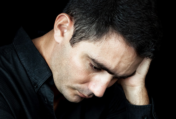 Man with head in hands suffering from loneliness