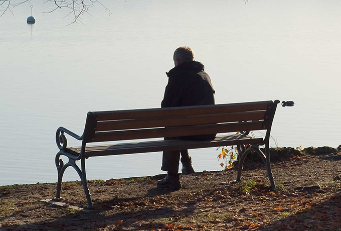 Man sitting alone on a park bench
