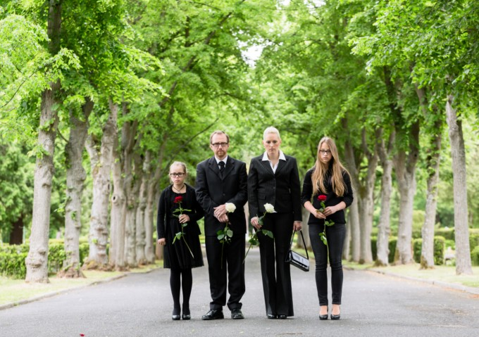 family grieving in cemetery