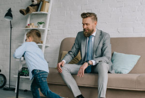 Man sat on the couch with child maintaining a good work-life balance