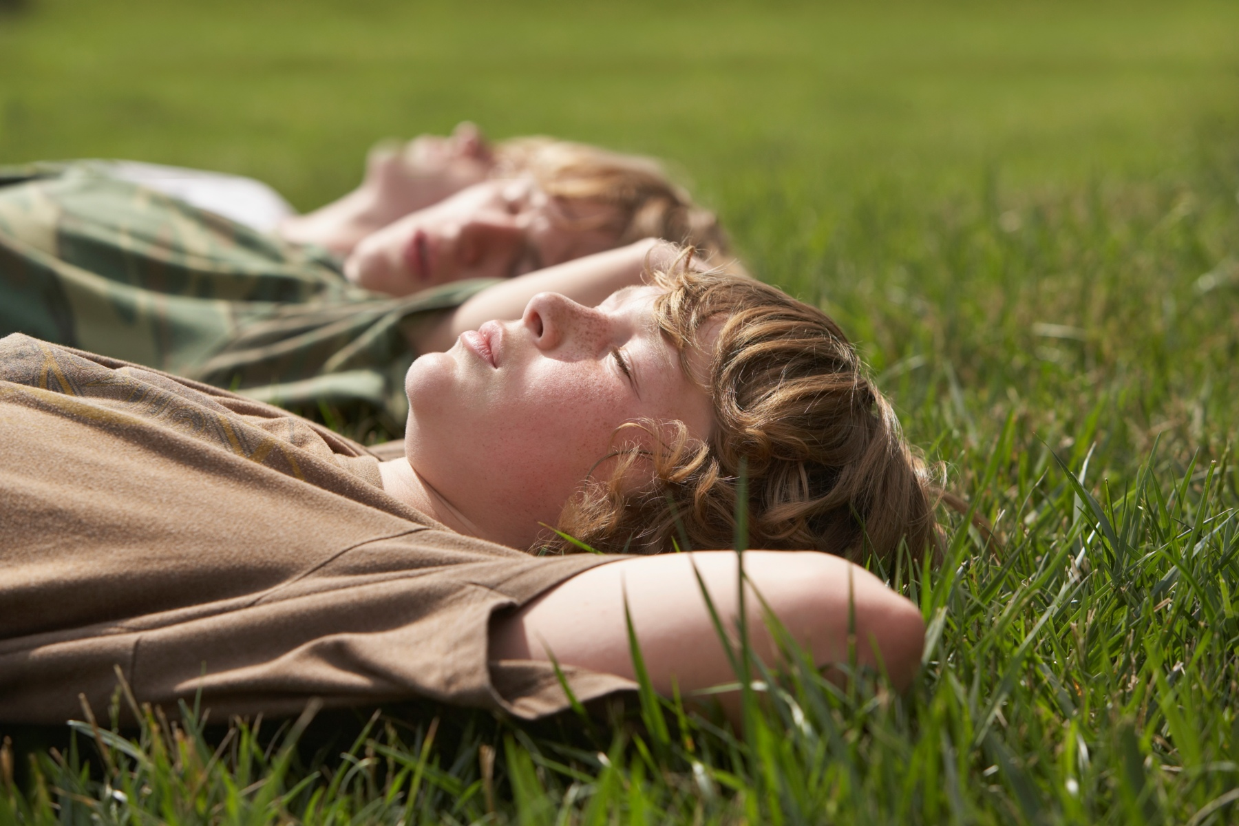 Young men trying mindfulness on grass