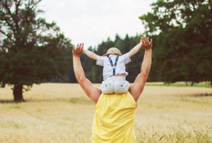 Man holding child on shoulders rural farm mental health
