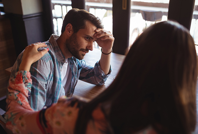 Suicide Prevention - Woman supporting a man at a cafe