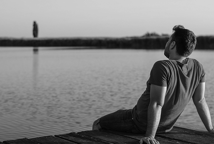 Man sitting on grass bank looking out to sea