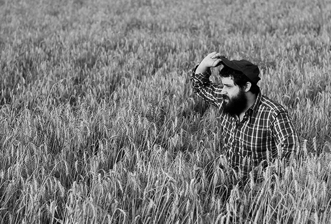 Farmer in a field looking at crops