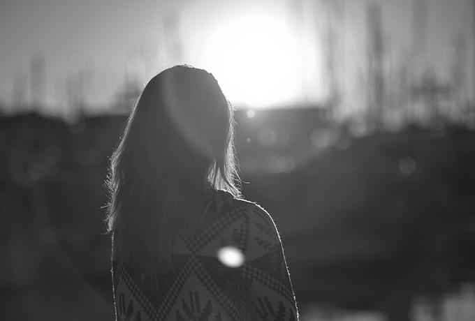 Woman walking through a field as sunsets