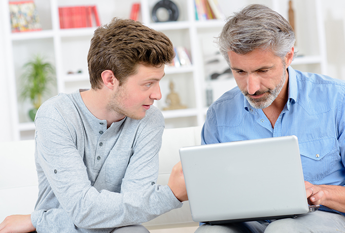 Father and son looking at a laptop