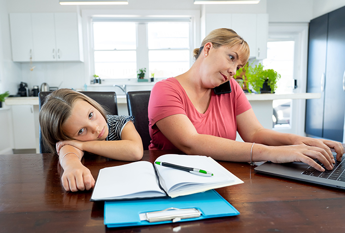 Young mother trying to work with her daughter at kitchen table